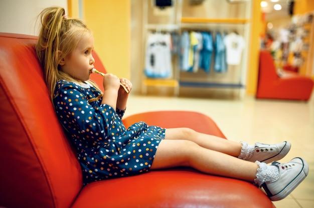 Hübsches kleines mädchen, das auf sofa im kindergeschäft sitzt