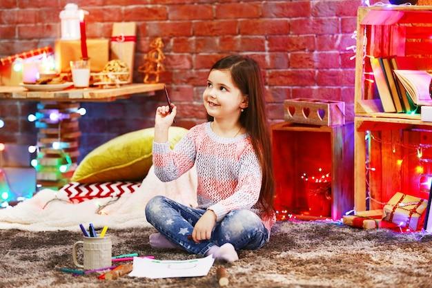 Hübsches kleines mädchen, das im weihnachtlich dekorierten raum malt