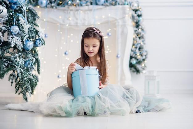 Hübsches kleines mädchen, das in der nähe von weihnachtsbaum drinnen sitzt.