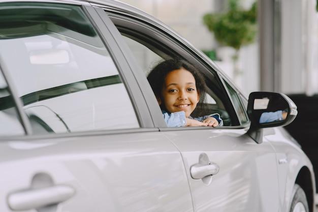 Hübsches kleines mädchen, das vom auto schaut. kind in einem autosalon.