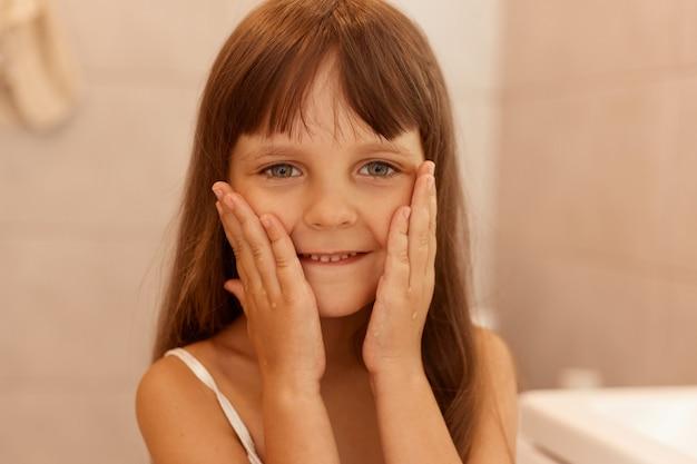 Hübsches kleines mädchen, das wangen berührt, die kamera mit einem angenehmen lächeln und positiven emotionen betrachtet, nach hygiene- und schönheitsverfahren im badezimmer posiert.