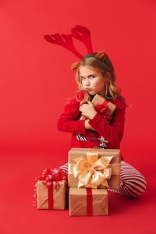 Hübsches kleines mädchen, das weihnachtshirschhörner trägt, die isoliert sitzen und stapel von geschenkboxen halten