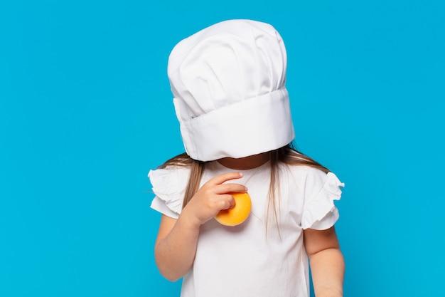 Hübsches kleines mädchen erschrockener ausdruck. kochen süßigkeiten konzept