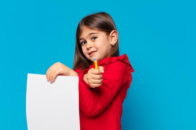 Hübsches kleines mädchen glücklicher ausdruck und ein blatt papier