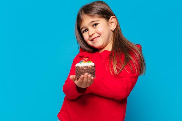 Hübsches kleines mädchen glücklicher ausdruck und hält einen tassenkuchen