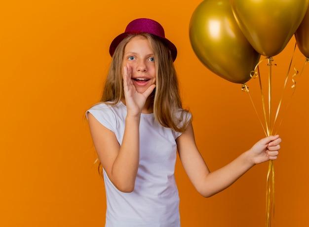 Hübsches kleines mädchen im feiertagshut, der bündelballons hält, die mit hand nahe mund schreien, geburtstagsfeierkonzept, das über orange hintergrund steht