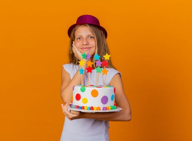Hübsches kleines mädchen im feiertagshut, der geburtstagskuchen hält, der mit glücklichem gesicht lächelt, geburtstagsfeierkonzept