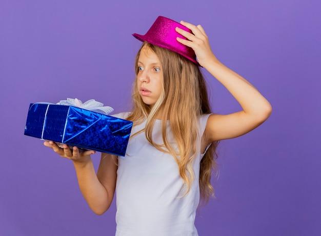 Hübsches kleines mädchen im feiertagshut, der geschenkbox hält, die es betrachtet, fasziniert ist, geburtstagsfeierkonzept, das über lila hintergrund steht
