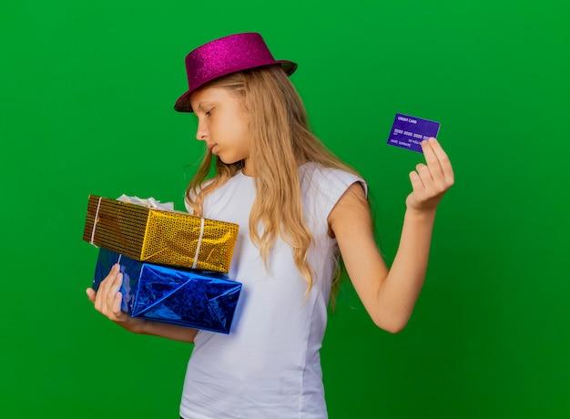 Hübsches kleines mädchen im feiertagshut, der geschenkboxen hält