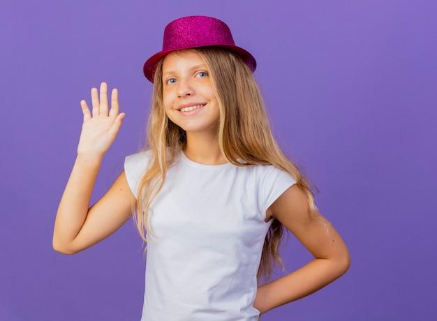 Hübsches kleines mädchen im feiertagshut, der mit hand glücklich und positiv, geburtstagsfeierkonzept, das über lila hintergrund steht, winkt