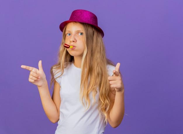 Hübsches kleines mädchen im feiertagshut, der pfeife mit zeigefingern auf kamera zeigt, geburtstagsfeierkonzept, das über lila hintergrund steht