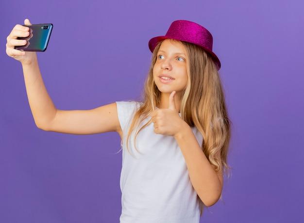 Hübsches kleines mädchen im feiertagshut, der selfie unter verwendung des lächelnden smartphones tut, zeigt daumen hoch, geburtstagsfeierkonzept, das über lila hintergrund steht