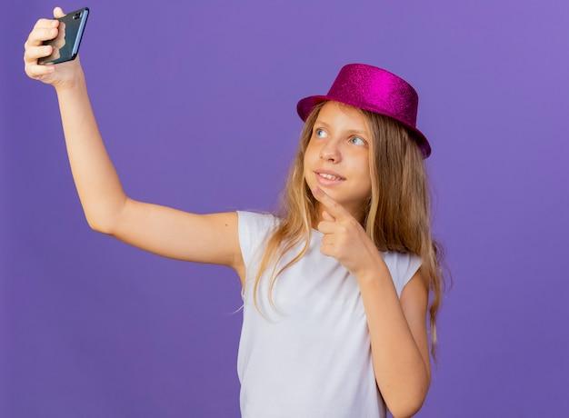 Hübsches kleines mädchen im feiertagshut, der selfie unter verwendung des selbstbewussten geburtstagsfeierkonzepts des smartphones tut, das über lila hintergrund steht