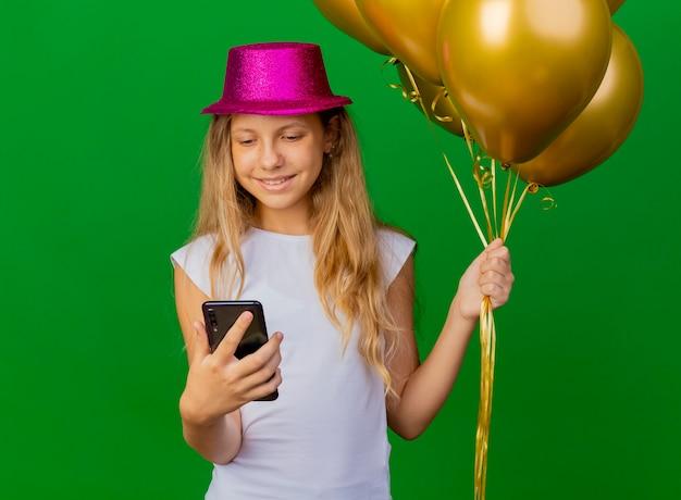 Hübsches kleines mädchen im feiertagshut, der smartphone hält