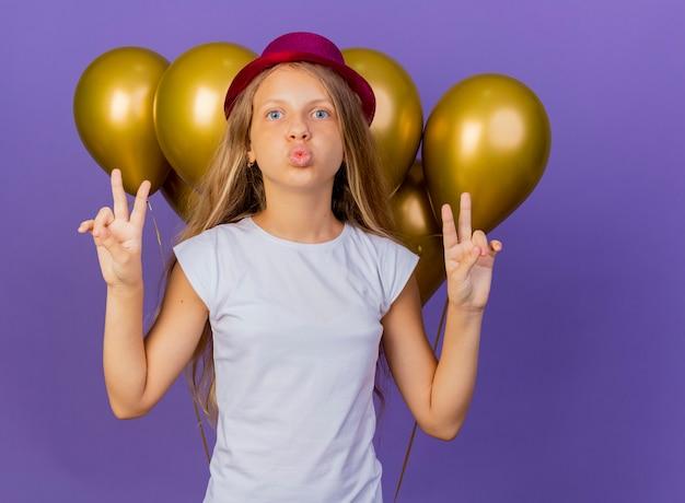 Hübsches kleines mädchen im feiertagshut mit bündel der luftballons, die kamera glücklich und positiv betrachten, die v-zeichen, geburtstagsfeierkonzept über lila hintergrund stehend zeigt