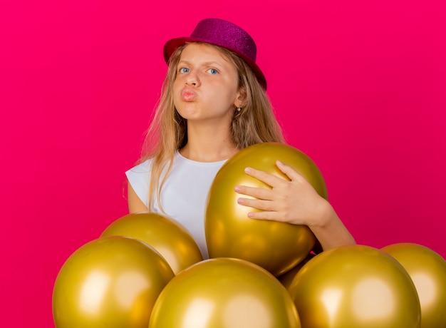 Hübsches kleines mädchen im feiertagshut mit bündel von ballons, die beiseite schauen einen blumenkuss, geburtstagsfeierkonzept stehend über rosa hintergrund