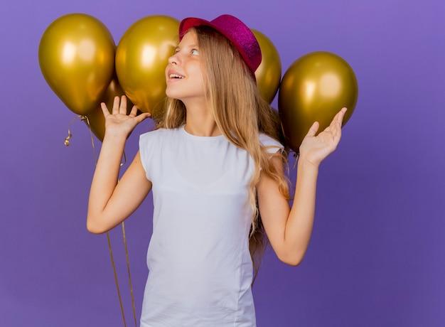 Hübsches kleines mädchen im feiertagshut mit bündelballons, die beiseite schauen mit glücklichem gesicht, geburtstagsfeierkonzept, das über lila hintergrund steht