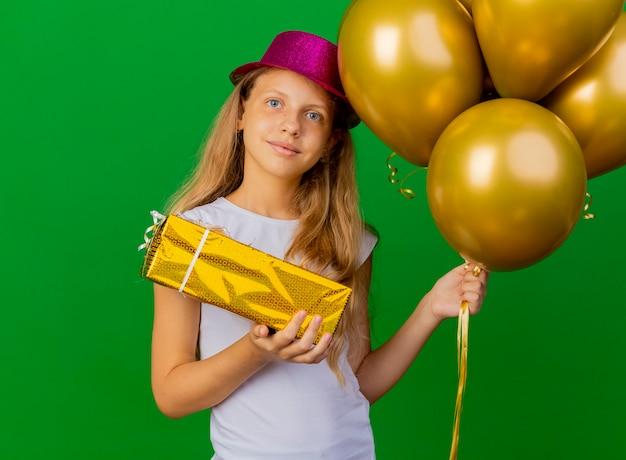 Hübsches kleines mädchen im feiertagshut mit luftballons