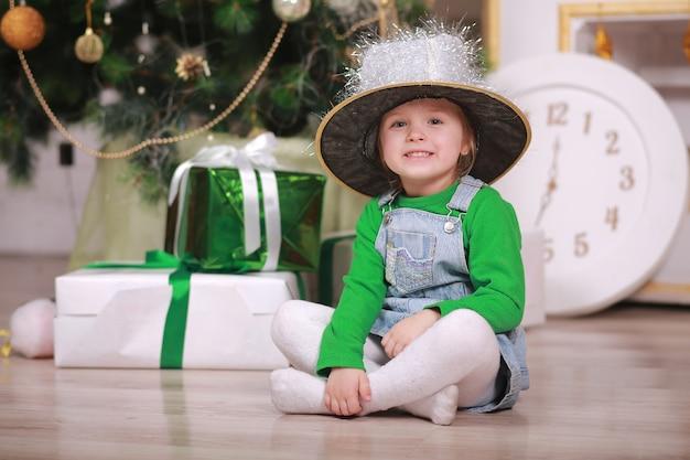 Hübsches kleines mädchen im glanzhut, der mit geschenk nahe dem weihnachtsbaum lächelt.