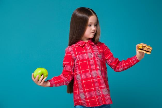Hübsches, kleines mädchen im karierten hemd mit brunethaar-griffburger