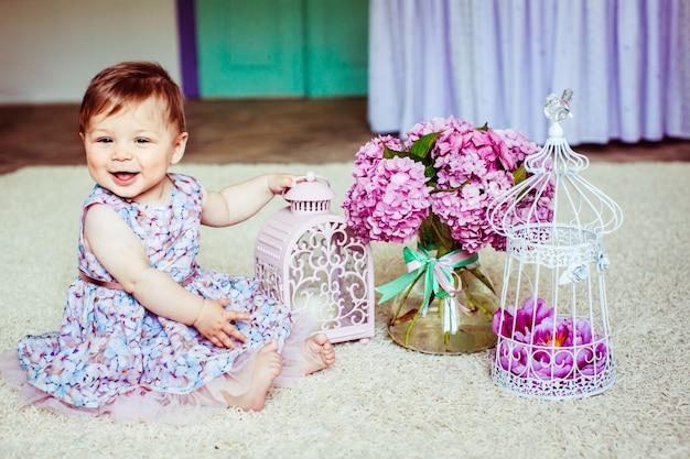 Hübsches kleines mädchen im kleid mit blumen sitzt vor rosa laterne und bouquet von flieder