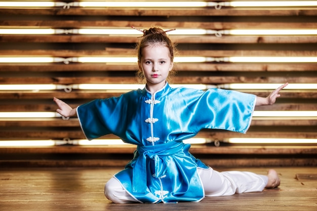 Hübsches kleines mädchen im raum in sportbekleidung für kampfsportarten ist wushu oder kung fu