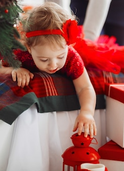 Hübsches kleines mädchen im roten kleid sieht lustig aus