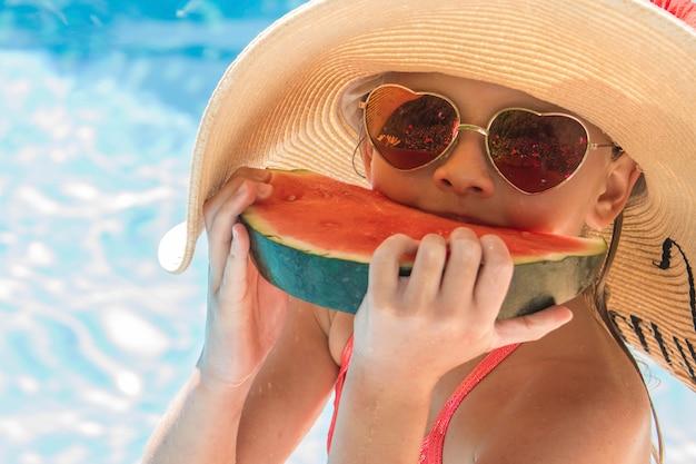 Hübsches kleines mädchen im schwimmbad, das wassermelone isst