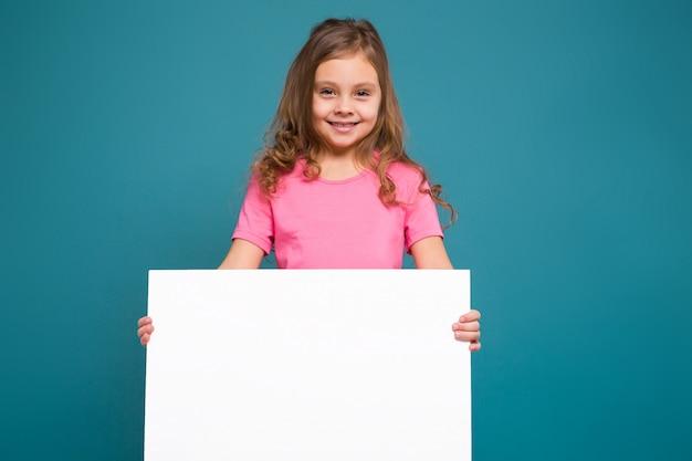 Hübsches, kleines mädchen im t-shirt mit braunem haar halten sauberes papier