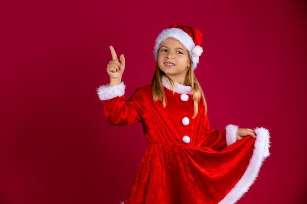 Hübsches kleines mädchen im weihnachtsmannkostüm und in der wintermütze. porträt des kindes, das das rote kleid von hand hält und den finger zeigt. isoliert auf roter wand mit freiem raum.