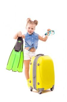 Hübsches kleines mädchen in blauem hemd, weißen shorts und sonnenbrille steht in der nähe des gelben koffers und hält maske und flossen
