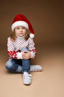 Hübsches kleines mädchen in kuscheliger kleidung und weihnachtsmütze sitzt auf dem boden, bild isoliert