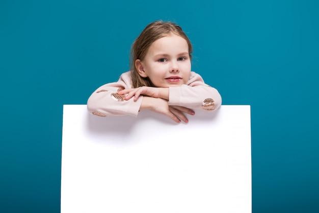 Hübsches, kleines mädchen in pullover mit brunet haar halten sauberes papier