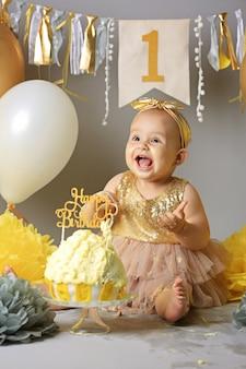 Hübsches kleines mädchen mit geburtstagstorte. nettes baby auf ihrer geburtstagsfeier. kuchen zerschlagen