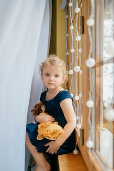 Hübsches kleines mädchen mit hellem haar im blauen kleid hält ihr schönes spielzeug und sitzt im babyzimmer auf einer fensterbank und lächelt
