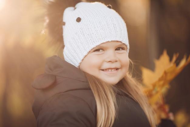 Hübsches kleines mädchen mit langen kastanienbraunen haaren und hübschem lächeln in schwarzer jacke geht im herbst im park spazieren