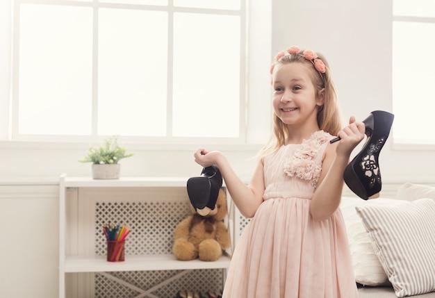 Hübsches kleines mädchen mit mamas schuhen. kleine fashionista wird high heels anprobieren, spaß zu hause haben, platz kopieren
