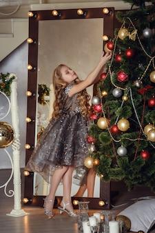 Hübsches kleines mädchen nahe dem neujahrsbaum. schönes mädchen im kleid nahe weihnachtsbaum, das auf feiertag wartet. innenraum mit weihnachtsdekorationen.