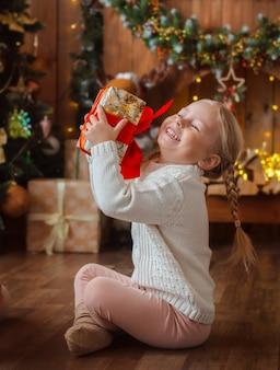 Hübsches kleines mädchen öffnet ein weihnachtsgeschenk.