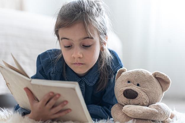 Hübsches kleines mädchen zu hause, das mit ihrem lieblingsspielzeug auf dem boden liegt und buch liest.