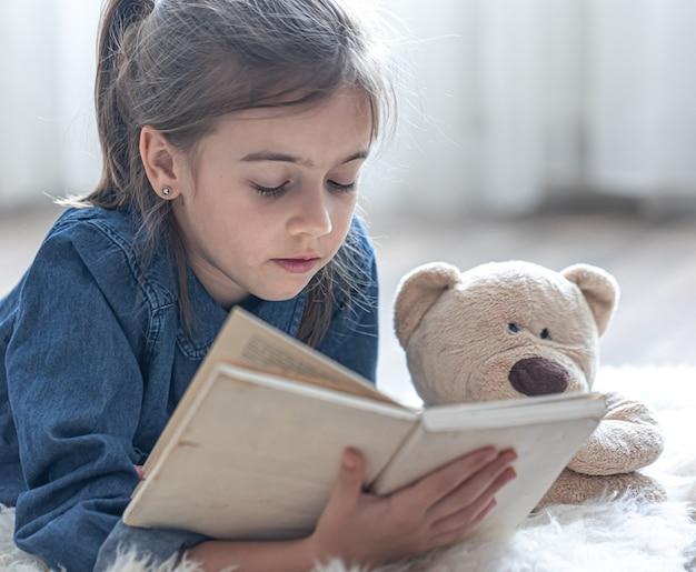 Hübsches kleines mädchen zu hause, das mit ihrem lieblingsspielzeug auf dem boden liegt und ein buch liest.