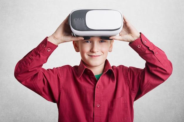 Hübsches kleines männliches kind trägt vr-brille, hat spaß und unterhält sich, spielt videospiele, isoliert über weiß