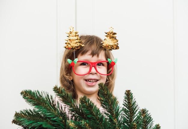 Hübsches kleinkindmädchen, das lustige weihnachtsbrille mit bäumen trägt. feiertage, neujahr und weihnachtskonzept.
