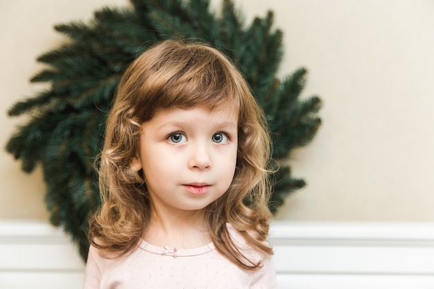 Hübsches kleinkindmädchen vor weihnachtskranz. feiertage, neujahr und weihnachtskonzept.