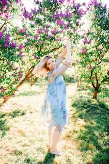 Hübsches lächelndes blondes mädchen, das im sonnigen park aufwirft