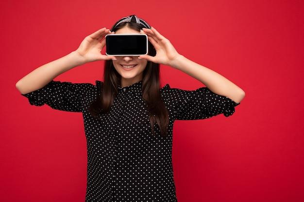 Hübsches lächelndes freudiges brünettes mädchen, das isoliert über roter wand steht und lässige stilvolle schwarze kleidung trägt, die handy mit leerem bildschirm für ausschnitt zeigt.