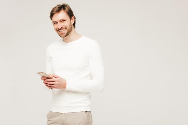 Hübsches lächelndes hipster lumbersexuelles geschäftsmannmodell, das weißen lässigen pullover und hosen trägt