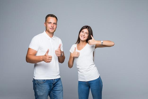 Hübsches lächelndes junges paar in lässiger kleidung daumen hoch isoliert auf grau