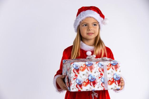 Hübsches lächelndes kaukasisches mädchen im roten hut und im kleid des weihnachtsmanns, das weihnachtsgeschenk in ihren händen hält und heraus schaut. isoliert auf weißer wand mit leerem raum.