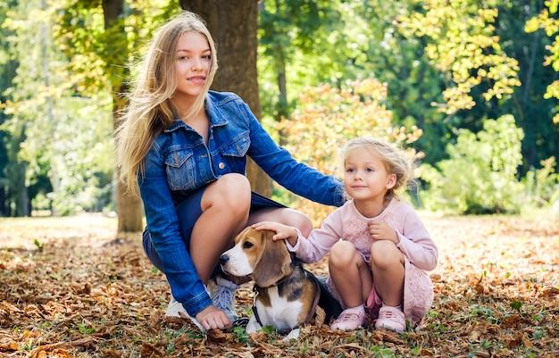 Hübsches lächelndes kleines mädchen, das mit einem beagle-hund sitzt
